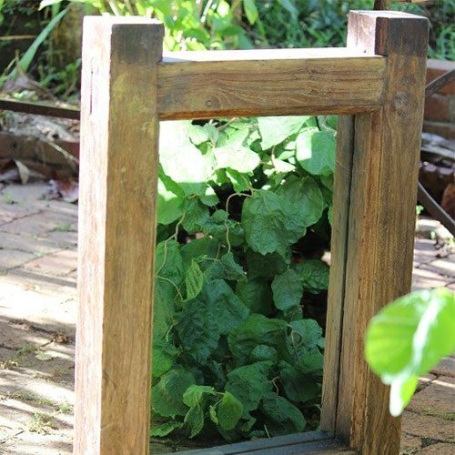 Aged timber garden mirror sitting on a walkway