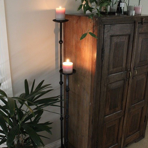 Candle stands with lit candles on them next to cabinet