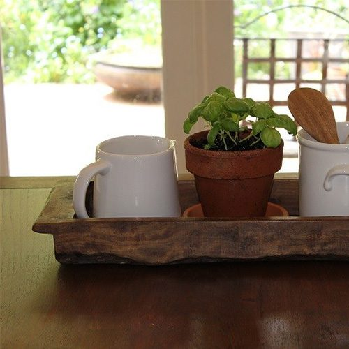 Mango Wooden Tray, sitting on a dining table with a view of the garden in the background.